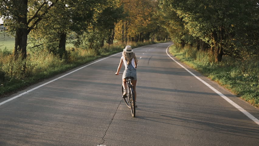 a young blonde girl in pants on retro bike going down the road in the field