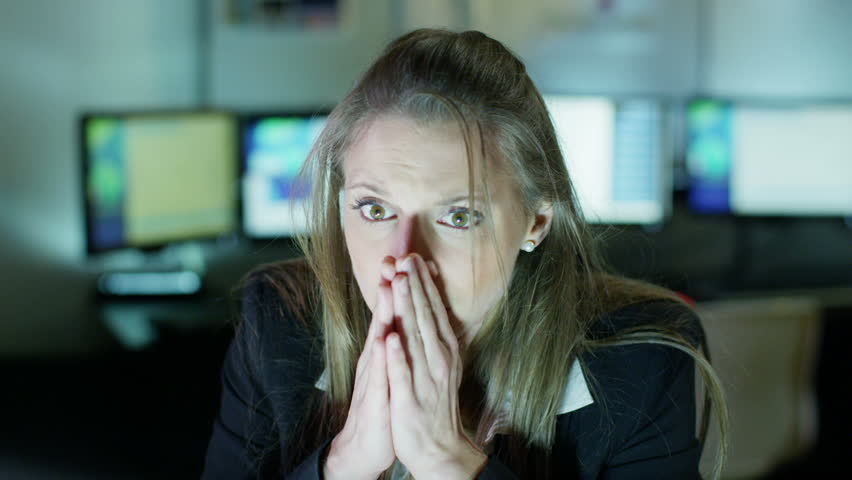 Attractive businesswoman working late at night on her own is shocked and distressed by something she sees on her computer screen