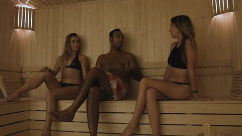 Group of young adults relaxing and having a conversation at sauna