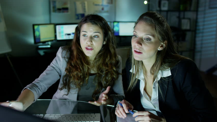 2 attractive female office workers are working late at night, a bank of computer screens can be seen in the background. Slow motion. | Shutterstock HD Video #3220231