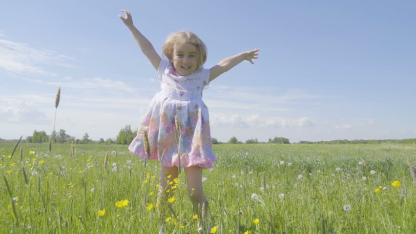 Cute little girl jumps in a meadow in the colors of a dandelion.. Joyful cheerful child laughing outdoors. Summer sunny day. Slow Motion. | Shutterstock HD Video #32206582