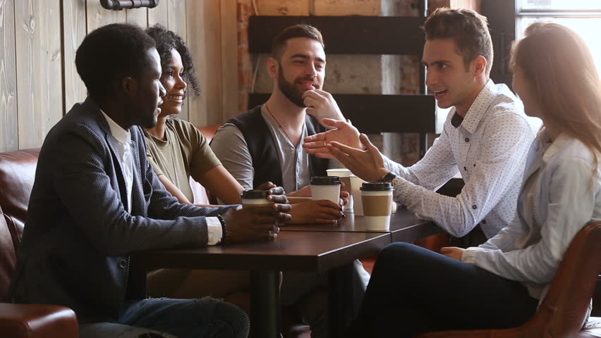 African and caucasian buddies making bet shaking hands at group meeting in coffeehouse, positive diverse young friends telling funny joke, laughing having fun while relaxing in cozy cafe with coffee | Shutterstock HD Video #32241922