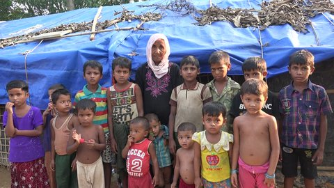TEKNAF, BANGLADESH - OCTOBER 25, 2017: A group of Rohingya refugee children with one old lady from Myanmar are standing in a group and looking helpless in the camera