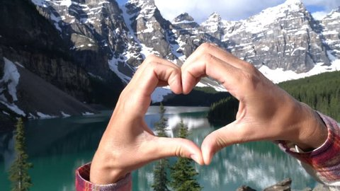Closed up of heart shape made with hands on beautiful mountain lake scenery  Young woman makes heart shape frame at Moraine lake, Banff National Park, Alberta, Canada