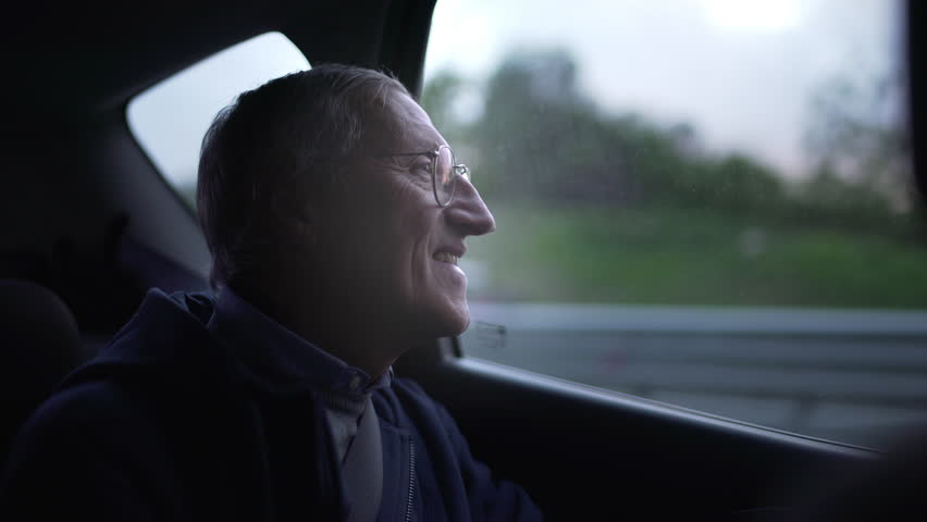 Happy mature man looking out of the window while she's traveling by car as a passenger at sunset.  | Shutterstock HD Video #32302012