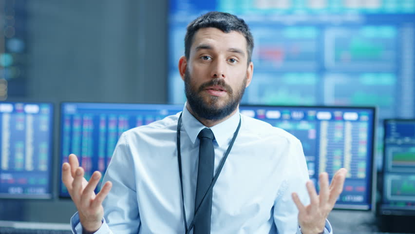 Professional Stock Market Trader Charismatically Talks into the Camera. Behind Him Computer Screens with Ticker Numbers, Data, Graphs. Shot on RED EPIC-W 8K Helium Cinema Camera. | Shutterstock HD Video #32305162