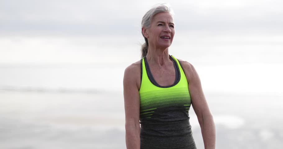 Senior woman checking activity tracker on a run