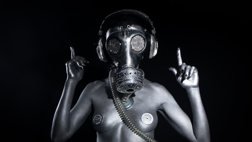 sexy woman dances in silver body paint with a gas mask covered in sparkling crystals. this is a special handmade item from our studio. how to survive the apocalypse in bling bling style