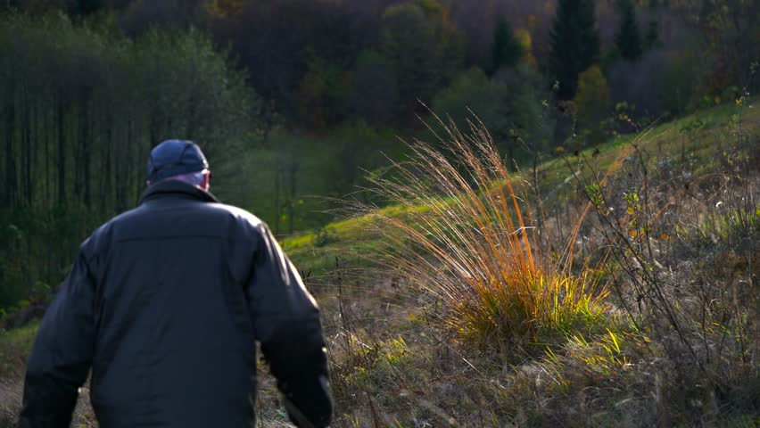Man goes in the wind under dry autumn grass