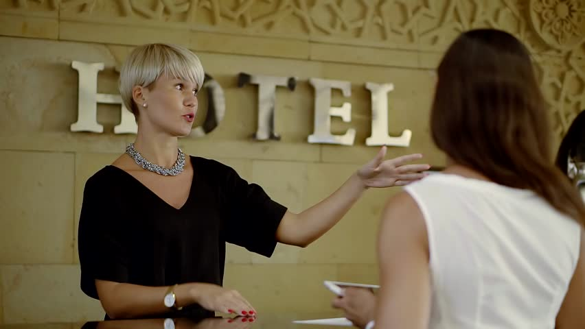 hotel manager is explaining client a rules of the hotel, showing by hands directions of main places