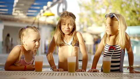 three children is having fun in a water park in summer, standing near an edge of pool with juicy drinks
