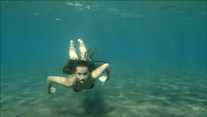 young woman swimming underwater to us