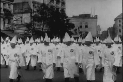 CIRCA 1920s - Members of the Ku Klux Klan, wearing glory suits, parade, with American flags, crosses and a Klansman dressed as Uncle Sam, through Washington, D.C., in 1928.