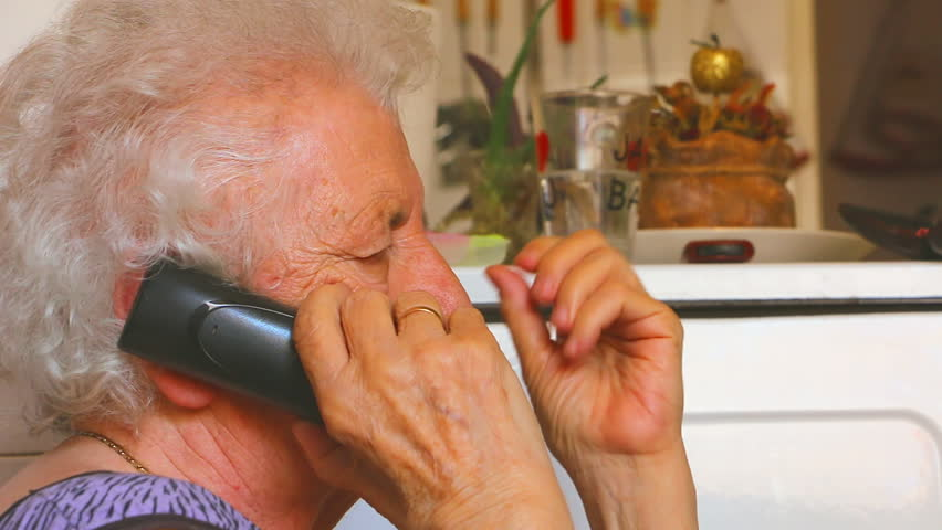 Old woman talking on the phone while she is sitting at home. Old woman talking on the wireless fixed phone