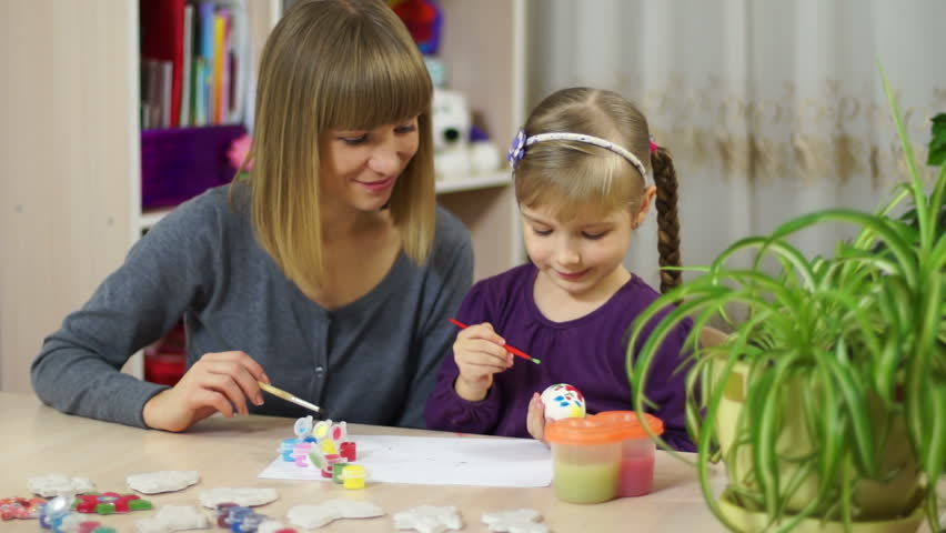 Mother and child decorate an Easter egg. Looking at camera