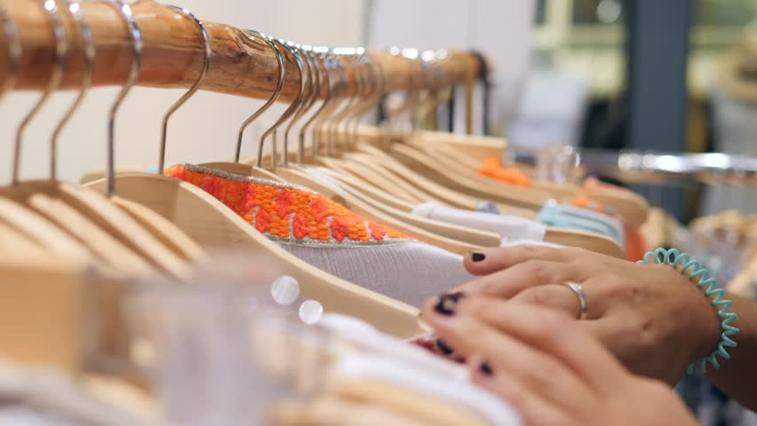 Female Hands Running on Clothing Hangers Rail Rack and Looking for Dress at Clothes Store. 4K. | Shutterstock HD Video #32375332