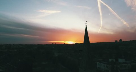 Aerial drone flight slowly orbiting a church steeple silhouetted against a bright orange sunset with the London (UK) skyline in the background.