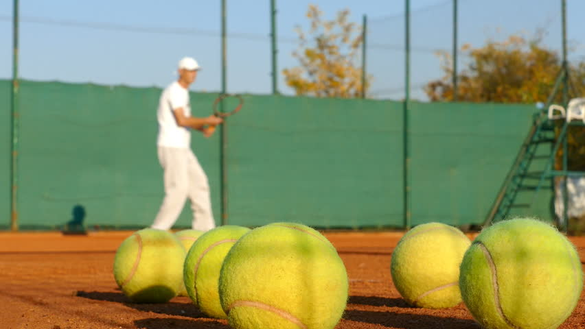 Man playing tennis on clay court, balls in front | Shutterstock HD Video #32378962