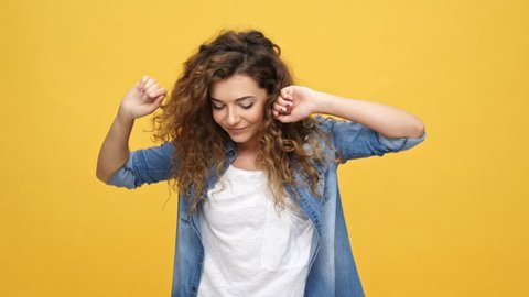 Happy carefree curly woman in denim shirt dancing and looking at the camera over yellow background