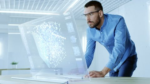 In the Futuristic Laboratory Creative Engineer Works on the Transparent Computer Display. Screen Shows Interactive User Interface with Neural Network, Artificial Intelligence Prototype.