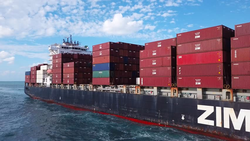 Mediterranean sea - October 25, 2017: Low angle view of a Large ZIM container ship at sea, loaded with various container brands - Aerial footage