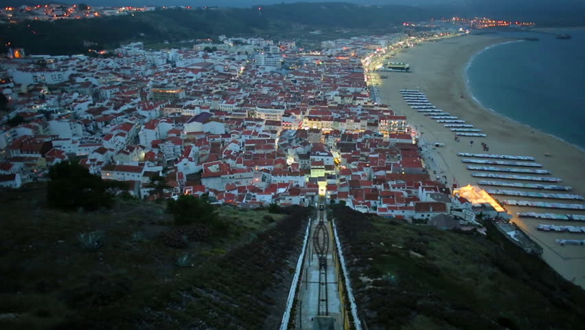 Time lapse panorama of Nazare in Portugal by night, the most popular seaside resorts in Silver Coast. Aerial view of skyline, beach and Ascensor da Nazare or Nazare Funicular from Nazare Sitio