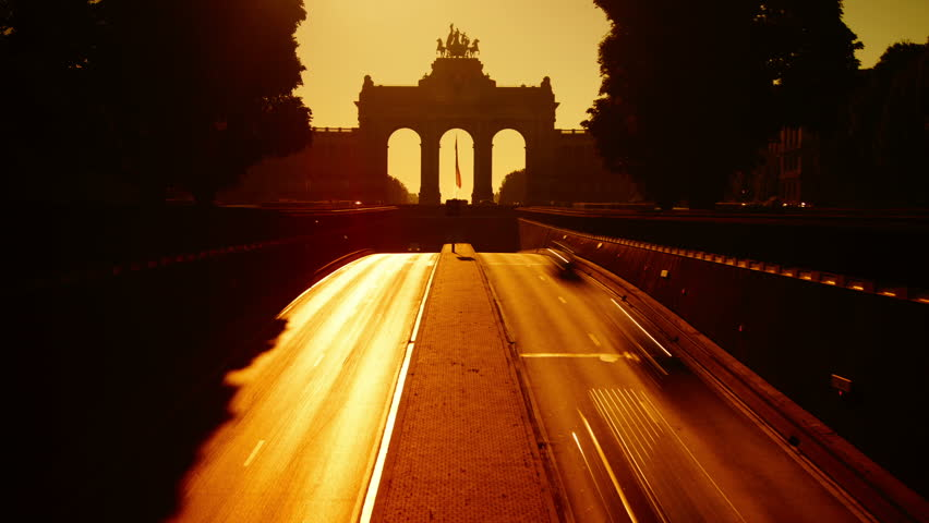 Brussels Cinquantenaire Park tunnel at morning. Cars drive in front of the landmark Triumphal Arch monument and the national flag of Belgium, time lapse