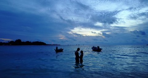 v13980 Two 2 sunset young people romantic couple sunbathing with drone aerial flying view on a beach with white sand and beautiful island background