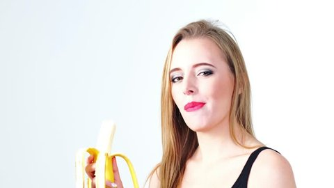 Attractive girl in shirt  eating banana,smiling and laughing.Isolated on white background.Red lipstick,healthy food, strong teeth concept.Close up.Contains sound.4K FOOTAGE