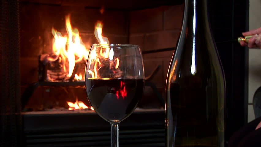 Radial Dolly Shot Of A Glass Of Red Wine With A Fire Burning In A ...