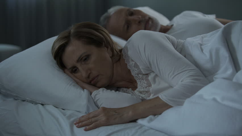 A Sleepless Man Lies Wide Awake In Bed While His Wife Is