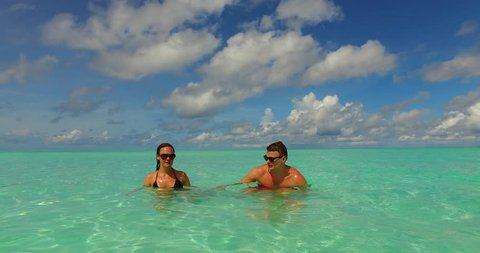 v15479 two 2 people together having fun man and woman together a romantic young couple sunbathing on a tropical island of white sand beach and blue sky and sea