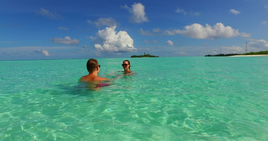 v15522 two 2 people together having fun man and woman together a romantic young couple sunbathing on a tropical island of white sand beach and blue sky and sea