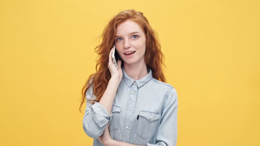 Happy ginger woman in denim shirt talking by the smartphone over yellow background