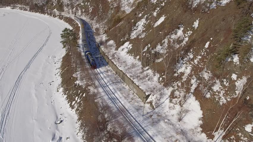 Passengers train Trans Siberian railway. Frozen lake Baikal coast. Winter beautiful Holiday  Russia. Sunny day snow field high rocks. Fast speed aerial drone 4k footage.