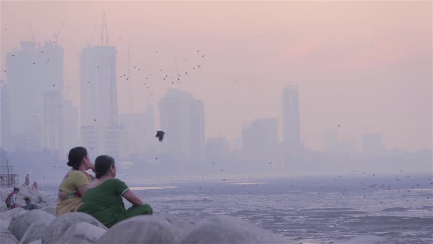 Two middle aged women sitting on tetra-pods and chatting next to the seashore. while group of crows flying and city skyline covered in smog visible in background in the morning, Mumbai, India (2017)
