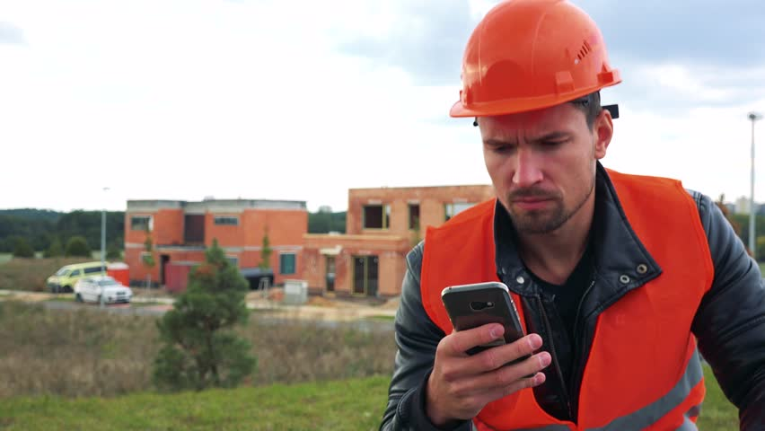 A young construction worker sits at a site and works on a smartphone - closeup - a house under construction in the background