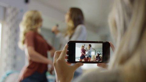Medium rack focus shot of girl photographing friends singing karaoke / Cedar Hills, Utah, United States
