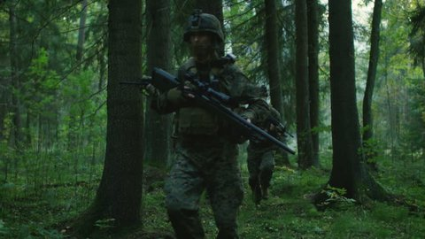 Fully Equipped Soldiers Wearing Camouflage Uniform Attacking Enemy, Rifles Ready to Shoot. Military Operation in Action, Squad Walking in Formation Through Dense Forest. Following Shot. 4K UHD.