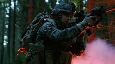 Squad of Five Fully Equipped Soldiers in Camouflage on a Reconnaissance Military Night Mission. They're Illuminated by Red Flare and Move Through Dense Forest. Shot on RED EPIC-W 8K Helium Camera.