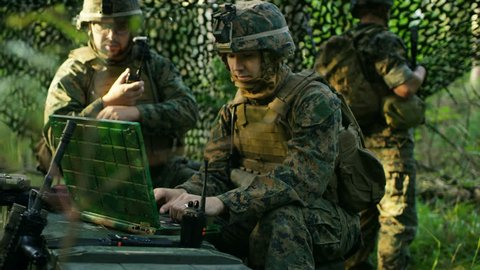 Military Staging Base, Officer Gives Orders to Chief Engineer, They Use Radio and Army Grade Laptop. They're in Camouflaged Tent in a Forest. They're on Reconnaissance Operation/ Mission. 4K UHD.