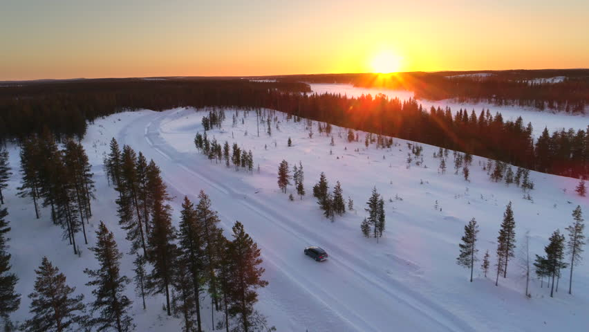 AERIAL: Flying above the car driving through snowy forest at golden winter sunrise. People on winter road trip traveling across snow covered Lapland wilderness at sunset. Car driving on empty icy road