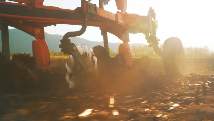 Close-up tracking shot of plow turning over soil in amazing sunset light.