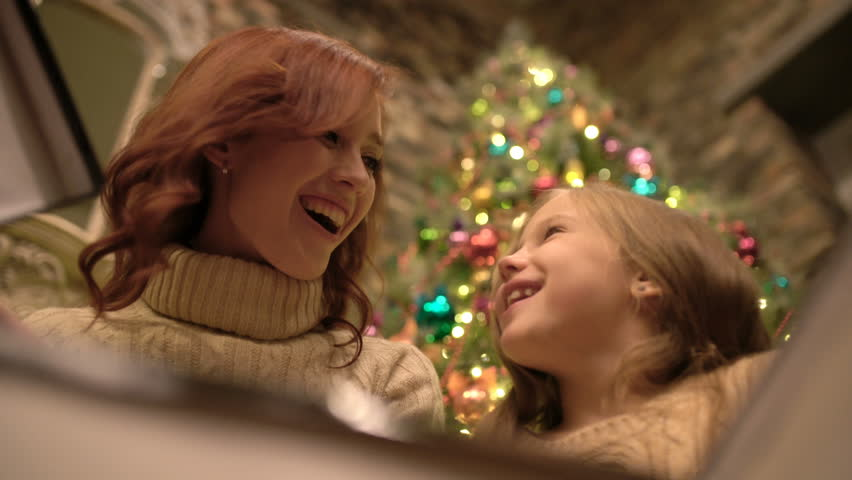 A young attractive woman all the same with her little sweet daughter open a gift, look inward and rejoice in the background of the Christmas tree, the view from inside the gift