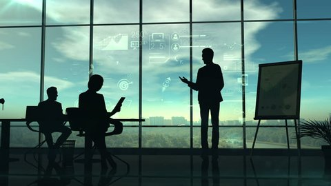The video shows the silhouettes of the speaker holding the corporate presentation and listeners.The action takes place in the office with huge glass windows in which the sun shines.