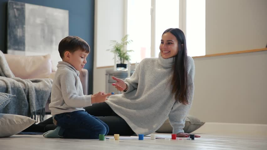 Mother with a child in the white interior of his house was opened the paint can sitting on the floor and dip your fingers in paint and draw on paper with your hands. Happy family | Shutterstock HD Video #32675536