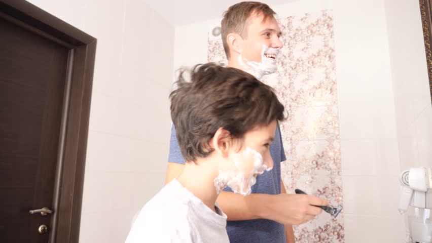 4K Father and son in the bathroom in the morning, little boy copies his father shaving. Slow motion.