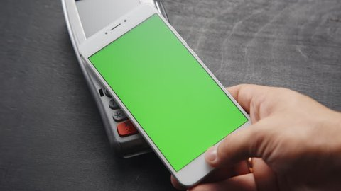 Top view of person using contactless payment with smartphone. Green screen template on phone.