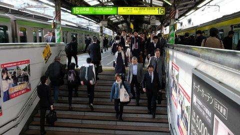TOKYO, JAPAN - NOVEMBER 10TH, 2017. Commuters climbing stairs at the Japan Railway  Shinjuku Station platform. Tilt shot.