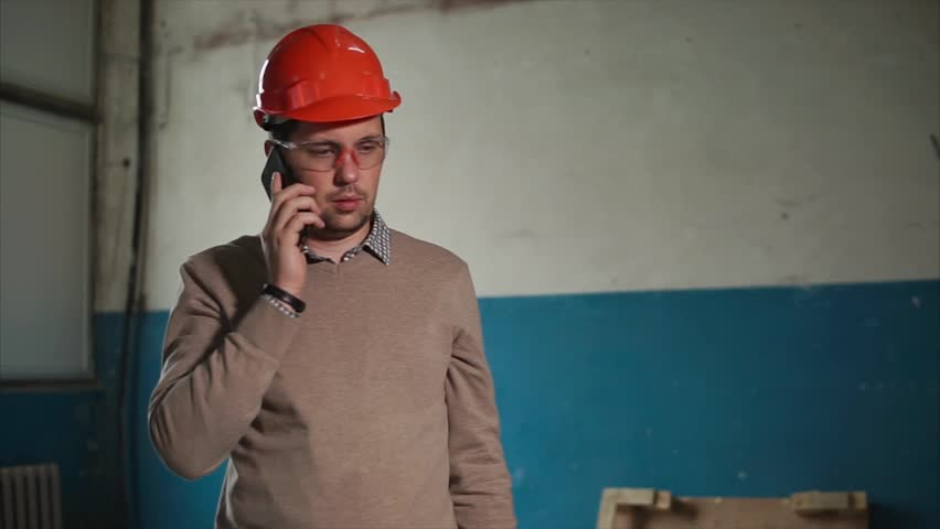 d29bbaa1729b4 Irritated engineer in hard hat having a mobile talk on business being at  the construction site